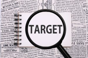 メモ帳に「TARGET」の文字。黒い縁取りのルーペが「TARGET」の文字を拡大している。」