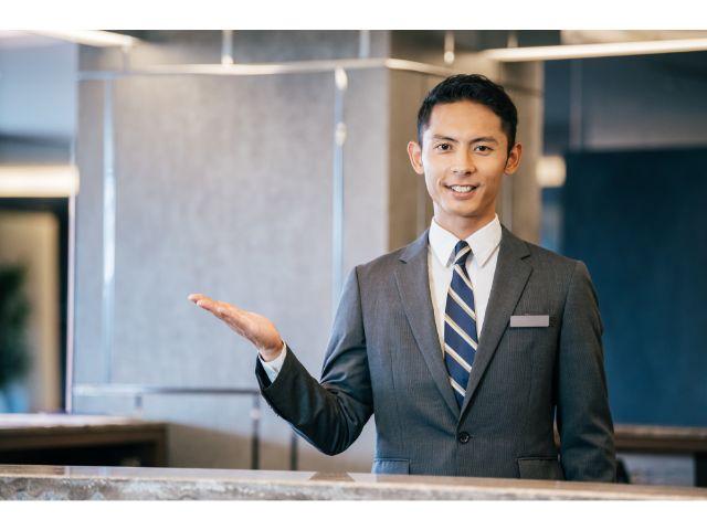 笑顔で右手を差し出す、スーツ姿の男性。