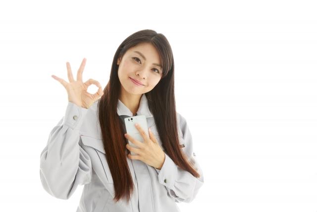 指でOKサインを出す女性