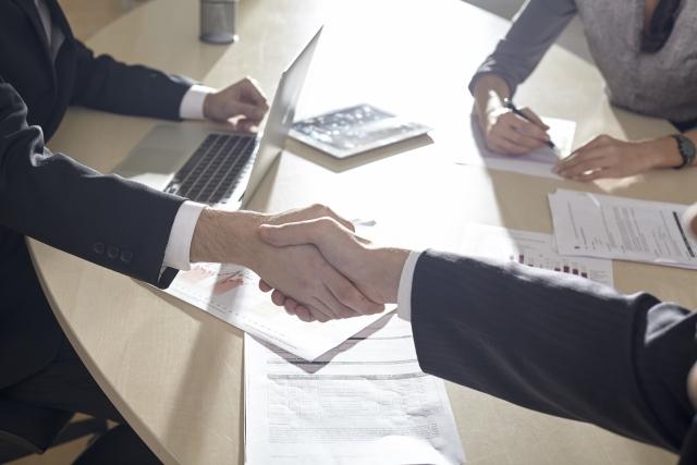 テーブルをはさんで握手を交わすスーツ姿の男たち