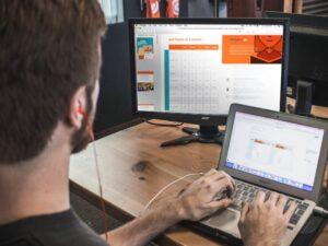 デスクトップPCとタブレットを操作する髭の男
