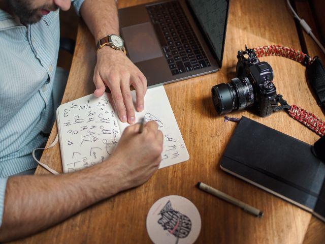 ノートに文字を書き留める髭の男性。傍らにはカメラとパソコン。