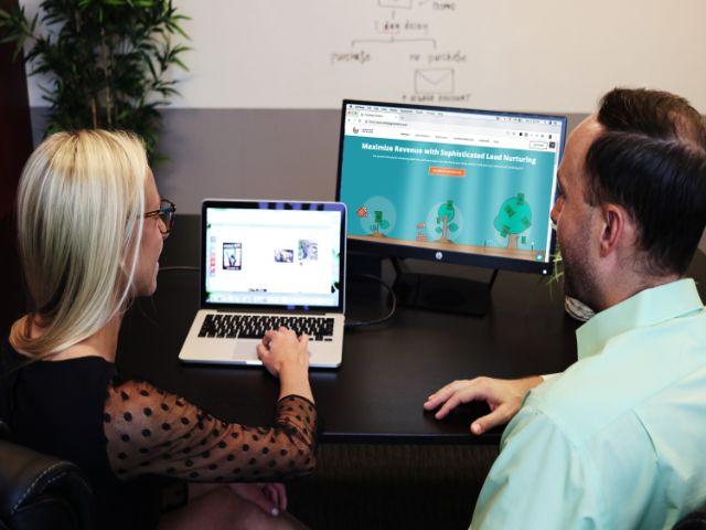 別々のパソコン画面に見入る男女