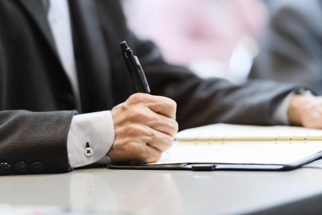 ボールペンで文字を書くスーツ姿の男性