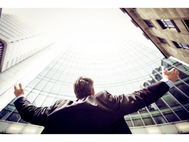 空に向かって両手を広げるスーツ姿の男性