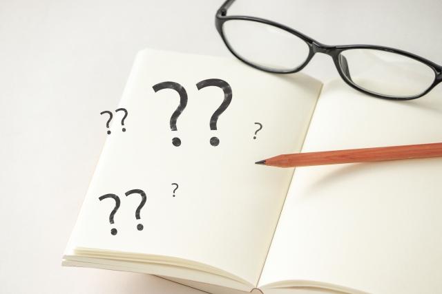 白紙のノートの上に黒縁眼鏡と鉛筆 3つの「??」」