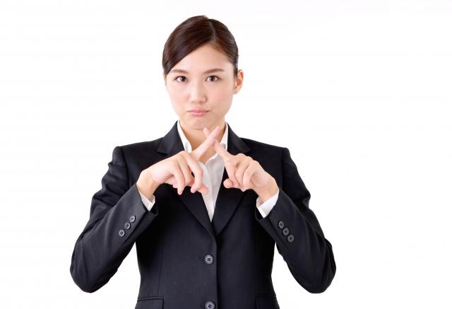 怒った顔で指でバッテンを作る女性