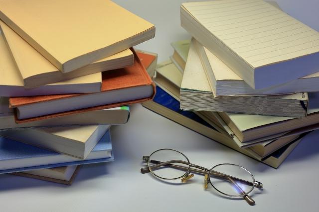平積みにされた書籍とメガネ