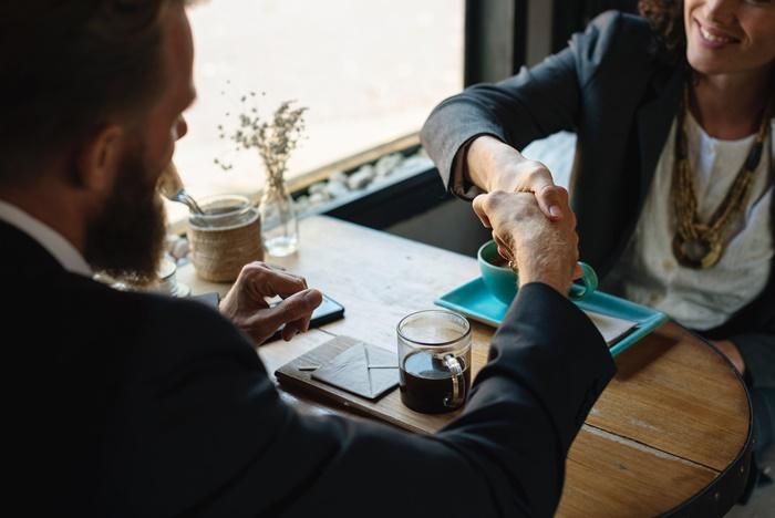 テーブル越しに握手するスーツ姿の男性