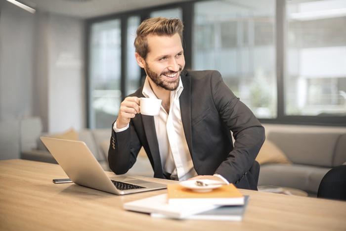 珈琲を飲みながら微笑む髭の男性
