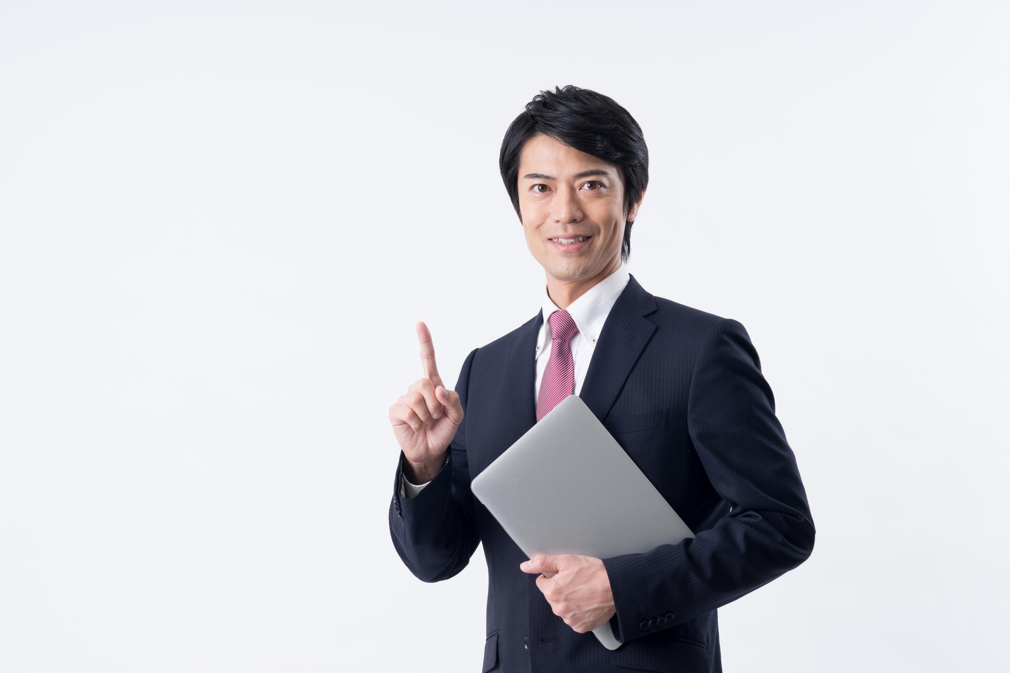 モバイルPCを抱え、人差し指を立てて微笑む男性