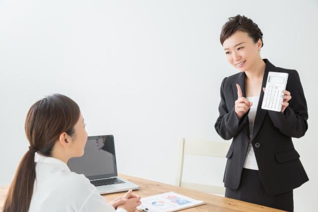 白衣の女性とタブレットを示して微笑む黒いスーツの女性