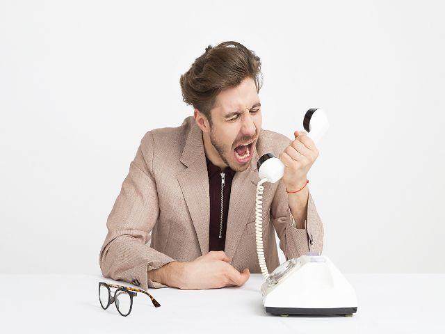 受話器に向かって怒鳴る男
