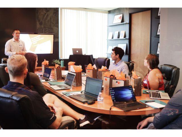 小テーブルを囲んで大画面のモニターに見入る人たち