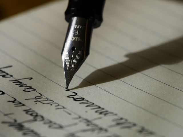 ノートに英文を書き連ねる万年筆