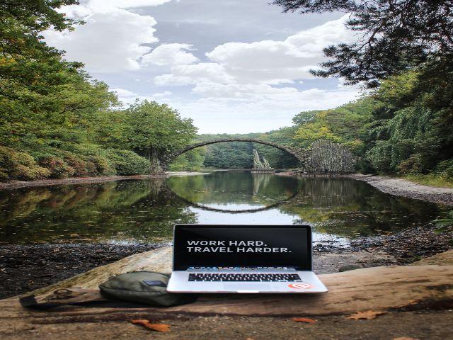 モバイルノートと背景に川にかかる橋