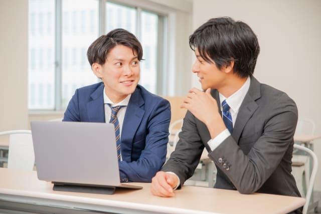 PCを前に、笑顔で語り合う2人のスーツ姿の男性