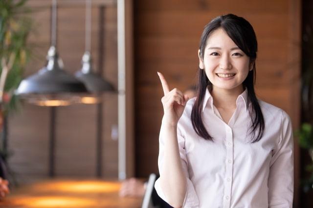 笑顔で右手の人差し指を出す女性。