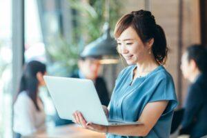 モバイルPCを腕に抱え、微笑みながら操作する若い女性