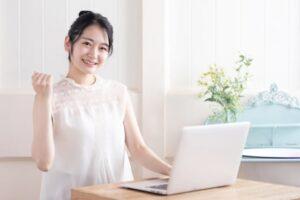 モバイルPCを開いて微笑む若い女性